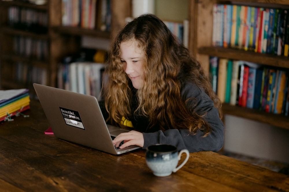 woman in black jacket using macbook pro