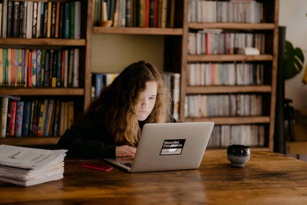 woman in black long sleeve shirt using macbook air on brown wooden table
