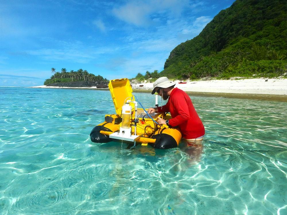 man in red shirt riding yellow kayak on sea during daytime