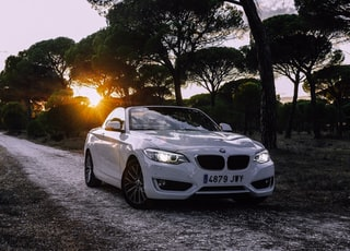 white bmw coupe parked on gray asphalt road during sunset