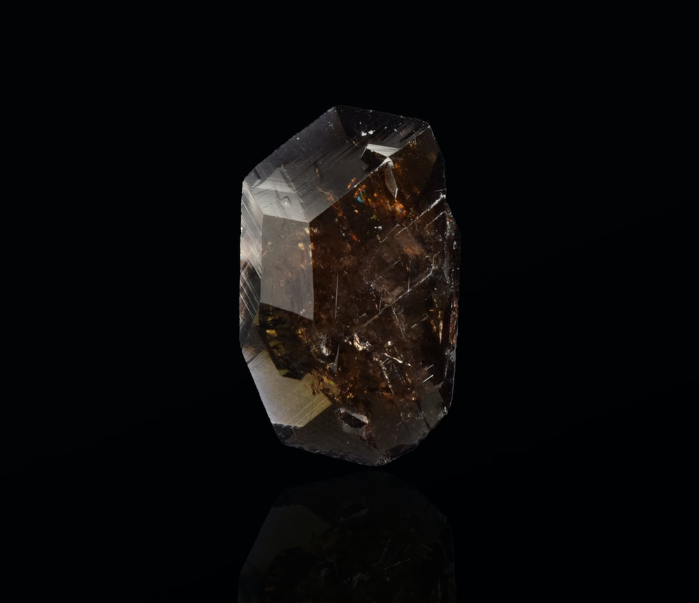 clear crystal stone on black surface