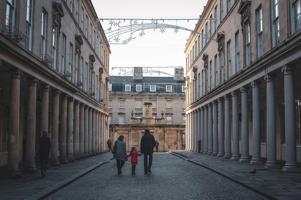people walking on sidewalk near building during daytime