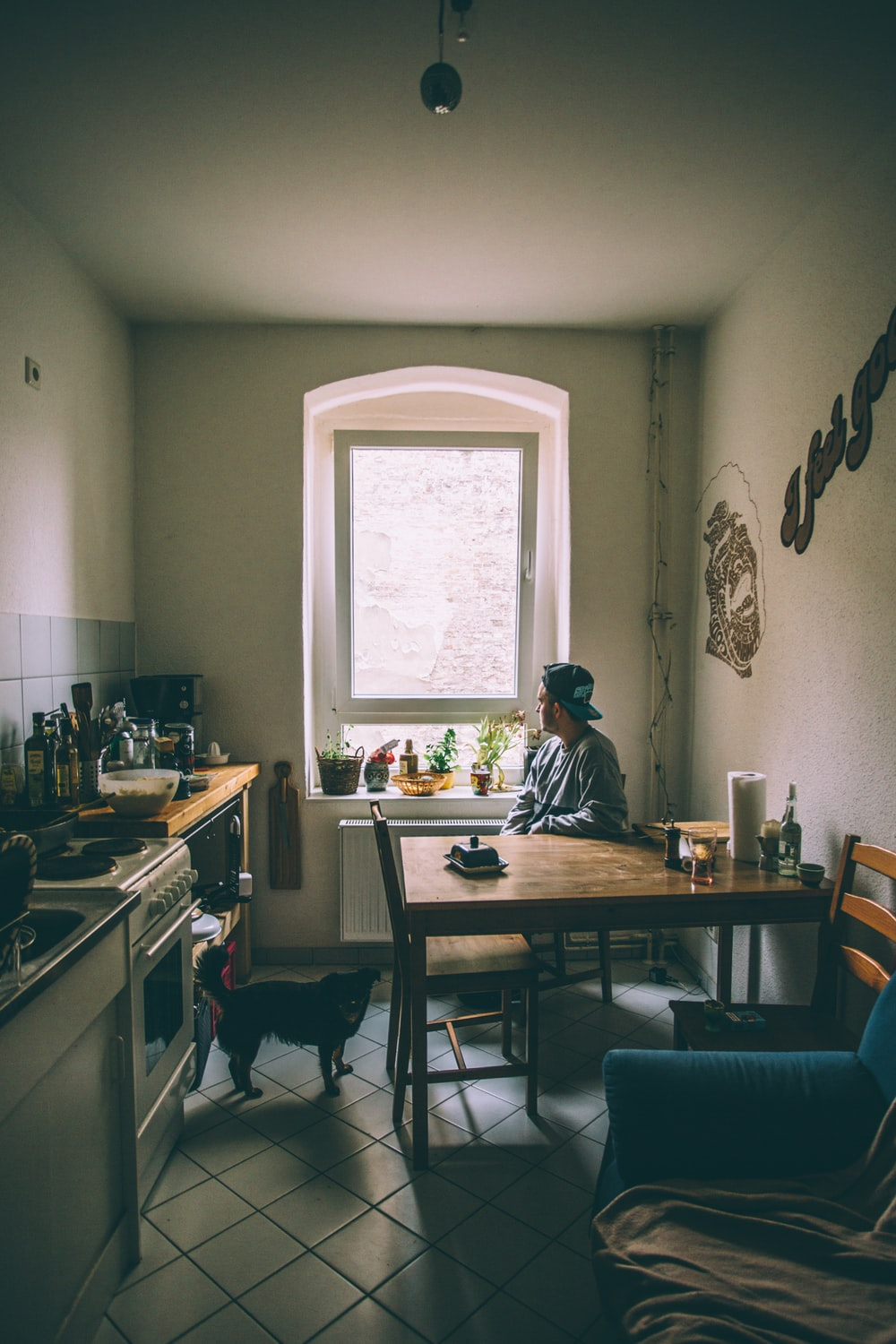 Man sitting a table with dog in a kitchen.