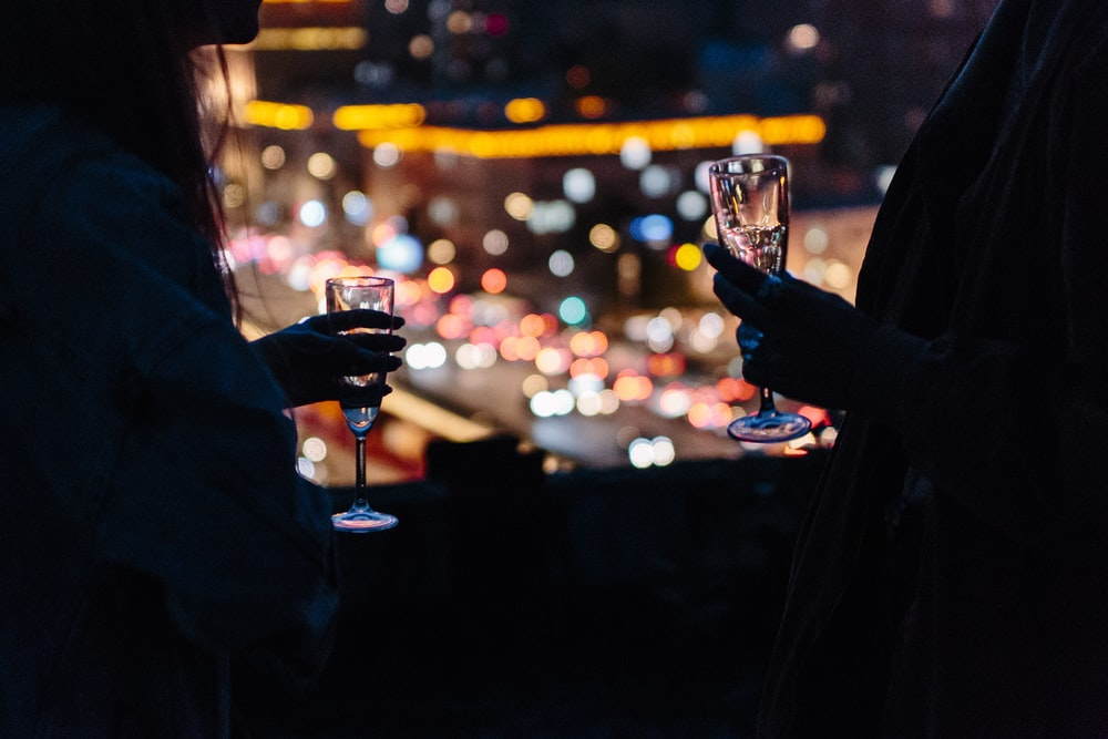 woman holding wine glass with bokeh lights