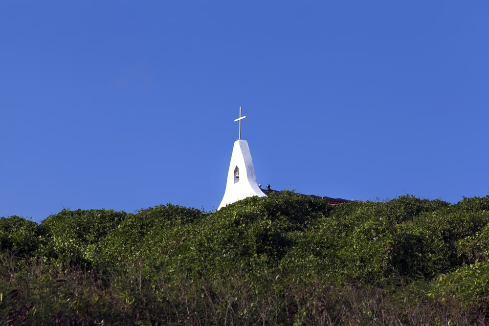 white church on green grass field under blue sky during daytime