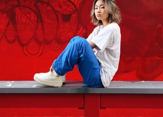 woman in white long sleeve shirt and blue denim jeans sitting on red wooden bench
