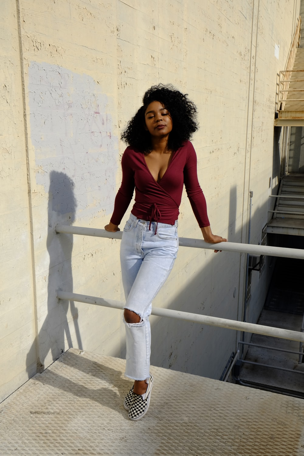 woman in red tank top and blue denim jeans standing on white concrete stairs