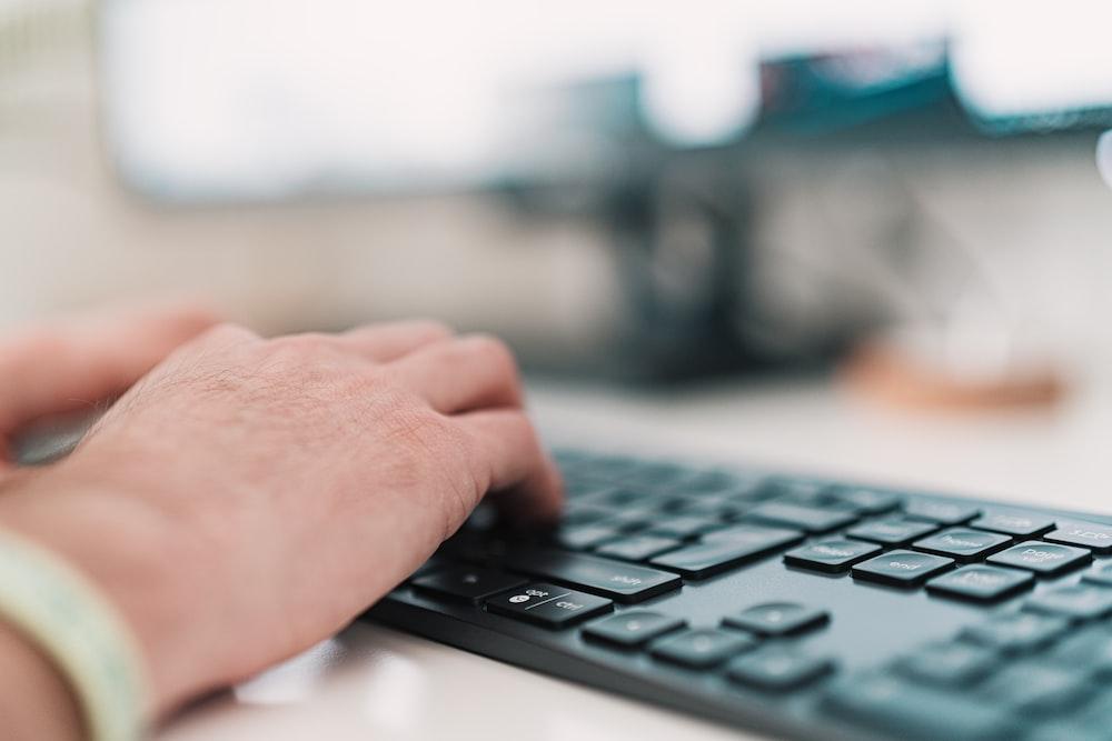person using black computer keyboard