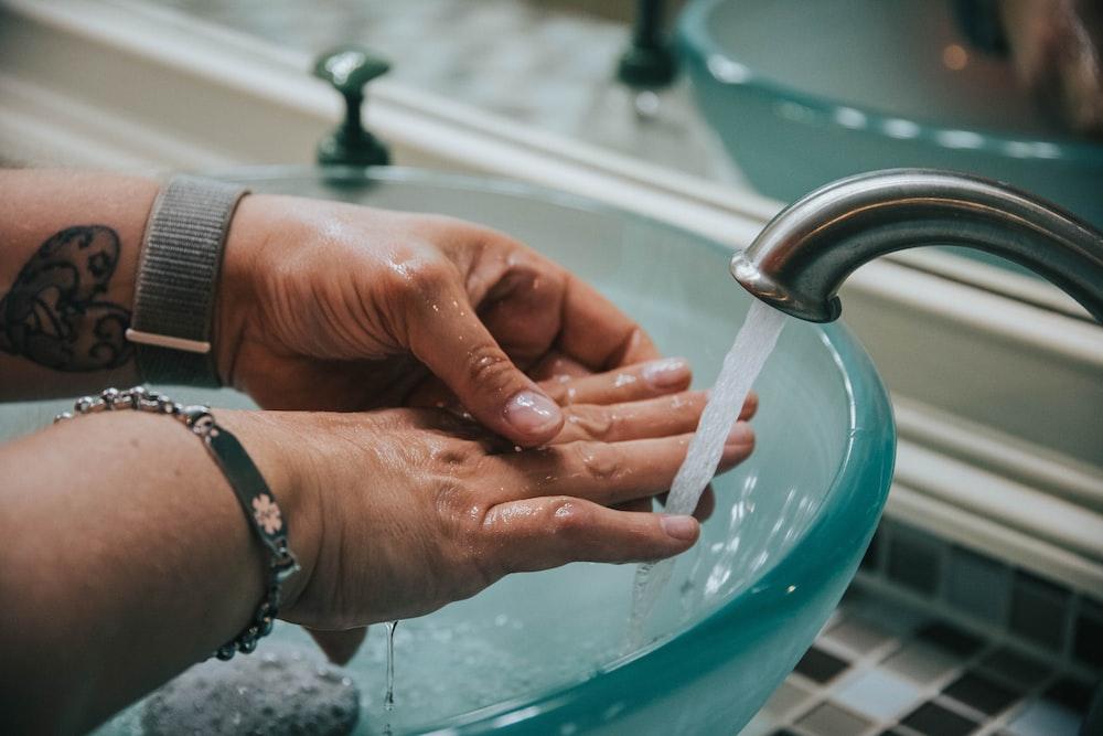 person washing hand on blue plastic basin