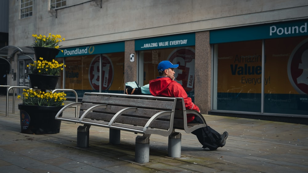 man in red jacket sitting on bench