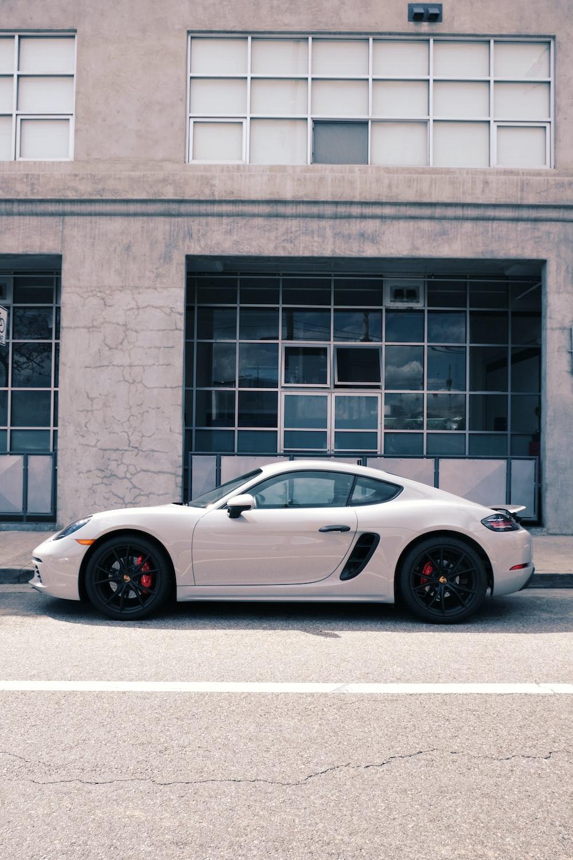 white porsche 911 parked near brown concrete building during daytime