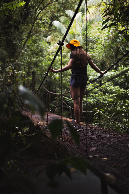 woman in black t-shirt and blue denim shorts walking on hanging bridge