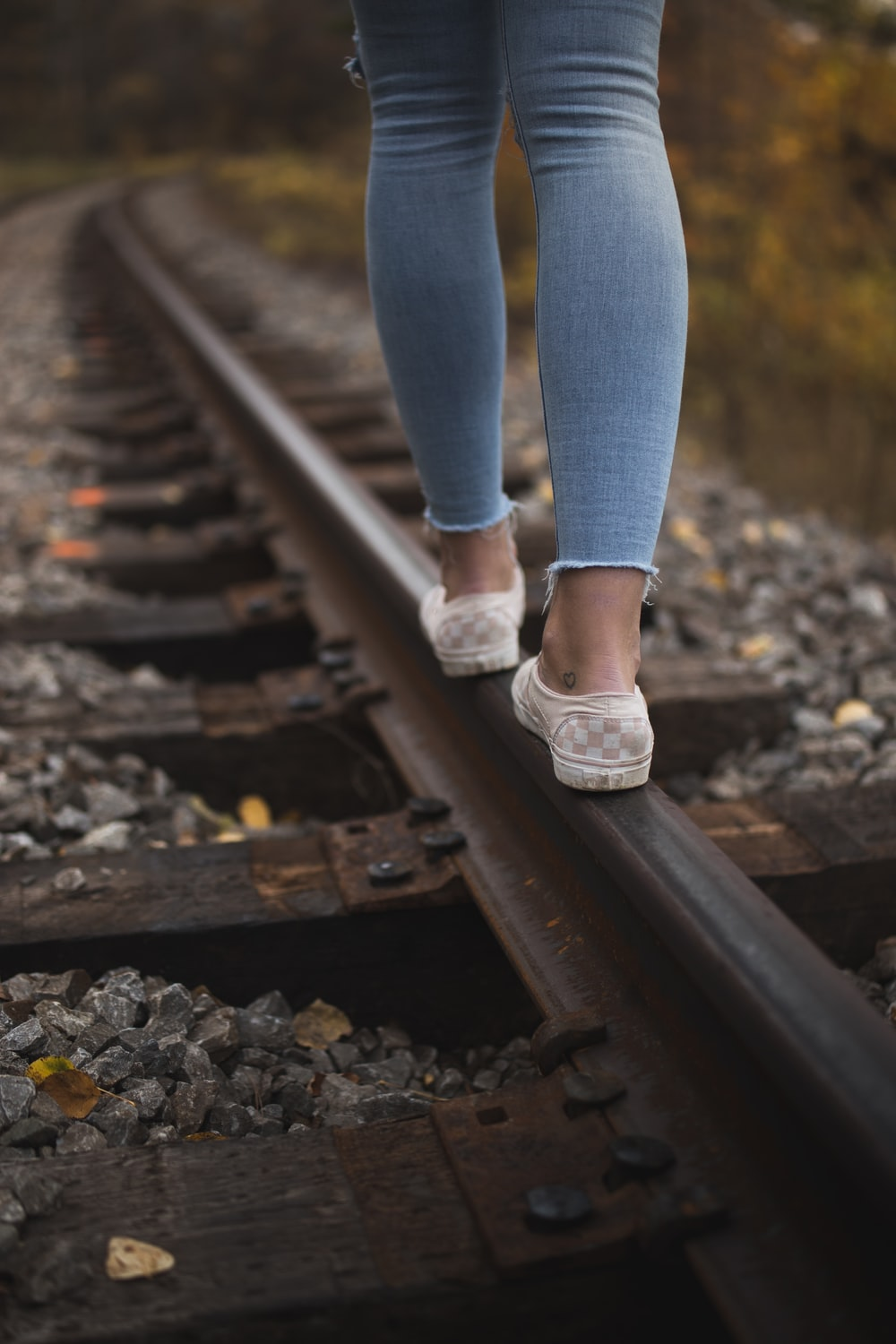 person in blue denim jeans and white low top sneakers standing on train rail during daytime