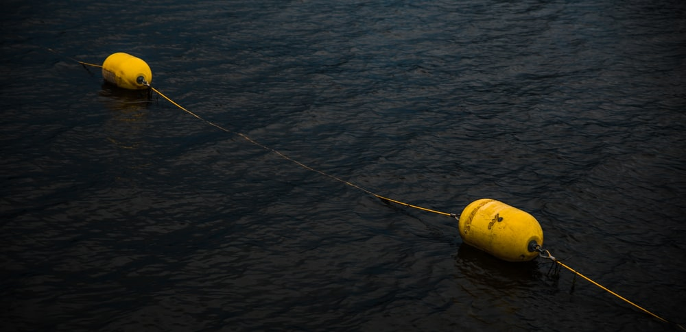 yellow and black fishing rod on body of water during daytime