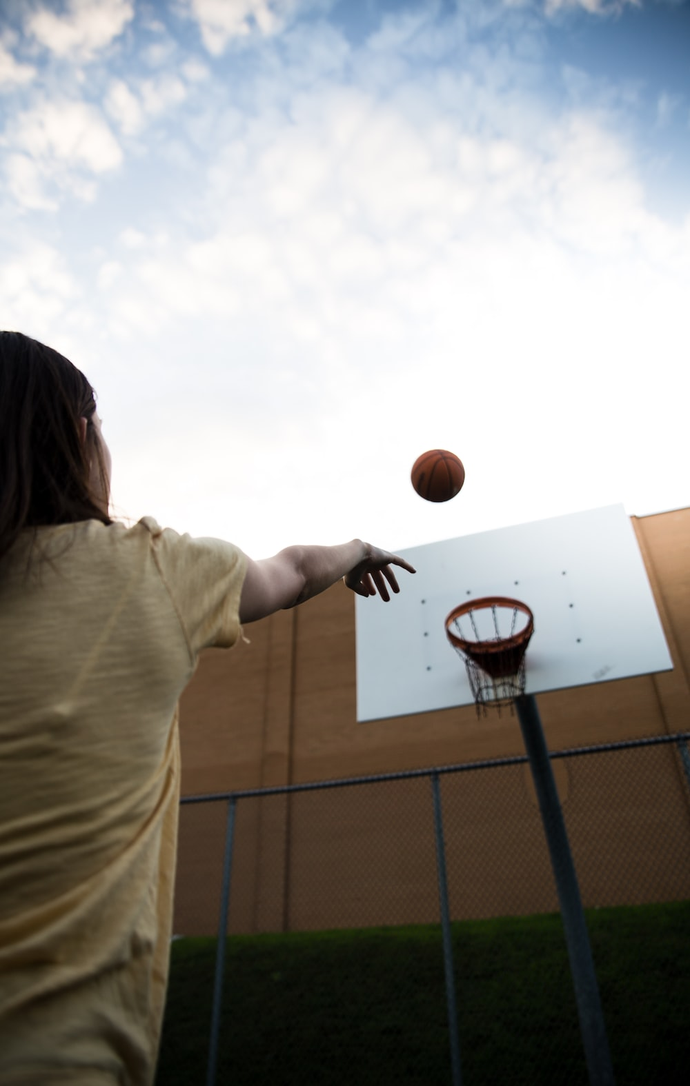 woman in white shirt holding basketball