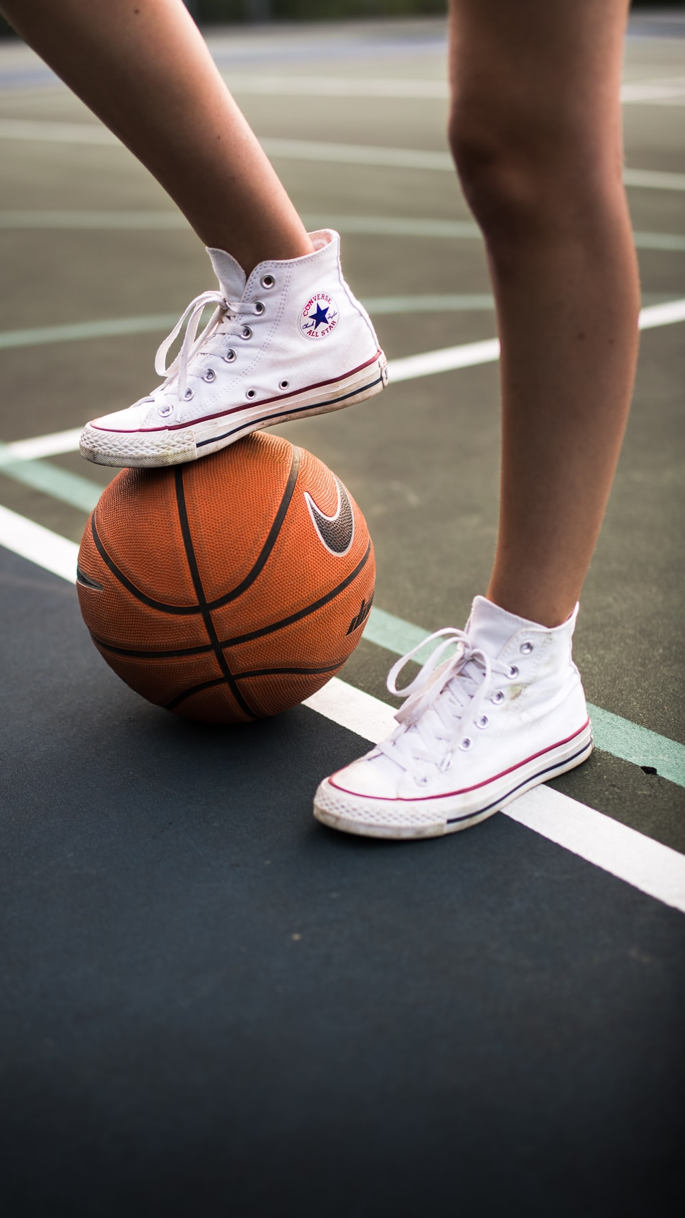 person in white nike basketball shoes standing on basketball court