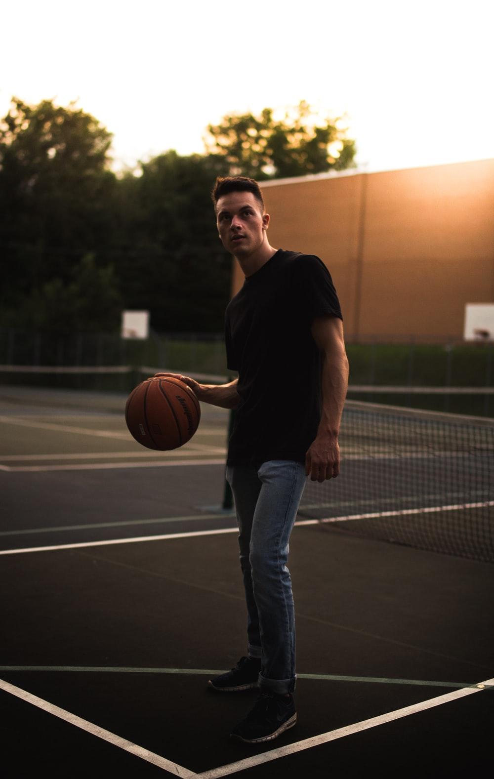 man in black crew neck t-shirt and blue denim jeans holding basketball during daytime
