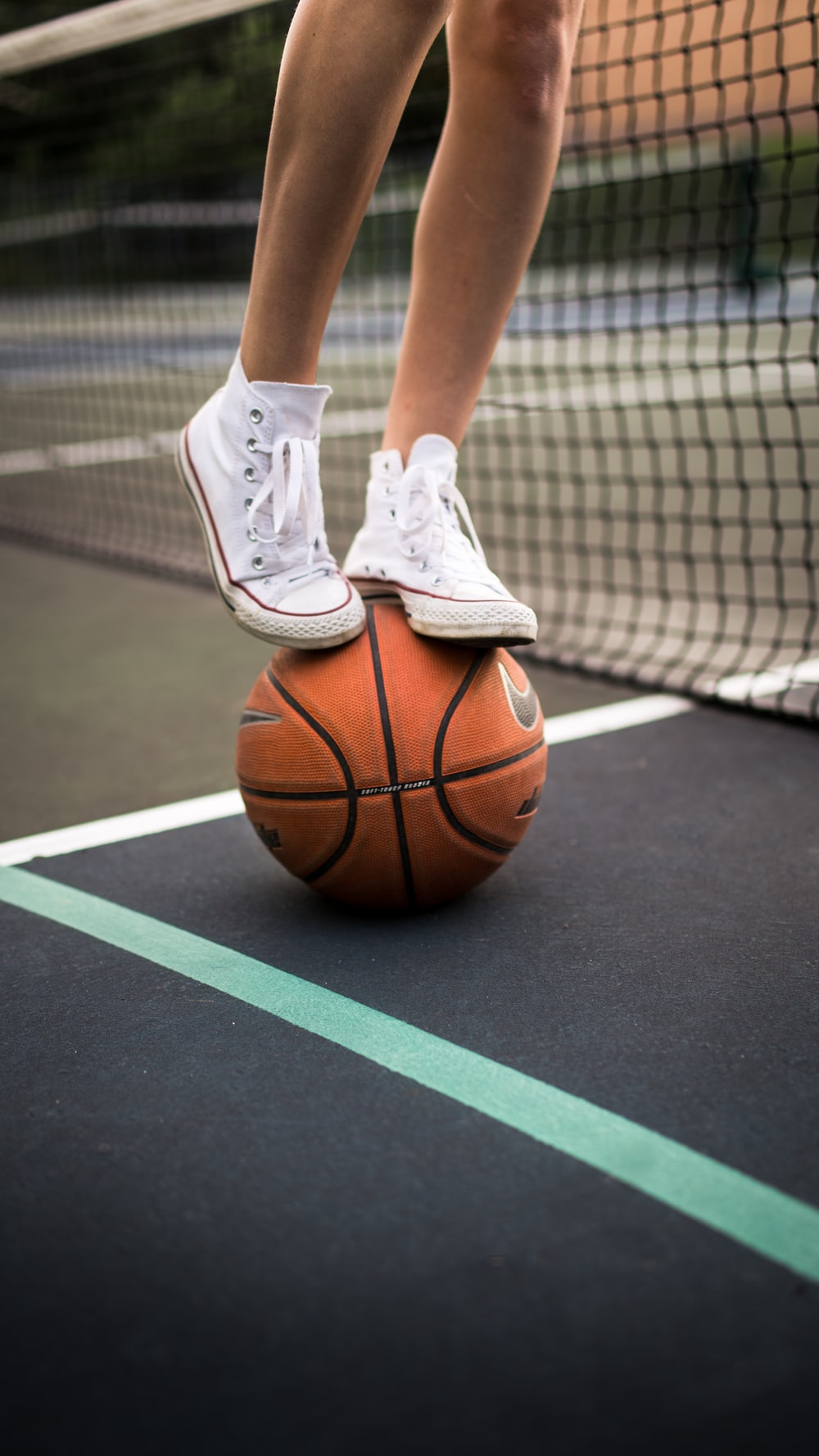 person in white nike athletic shoes standing on basketball court