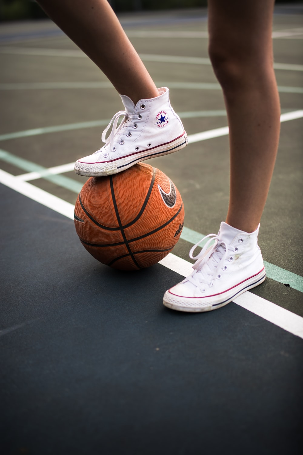 person in white nike basketball shoes and white nike basketball shoes