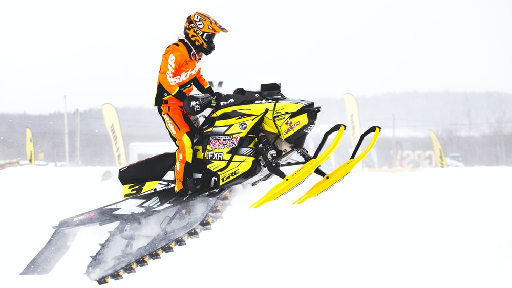 man in orange jacket riding yellow snow mobile