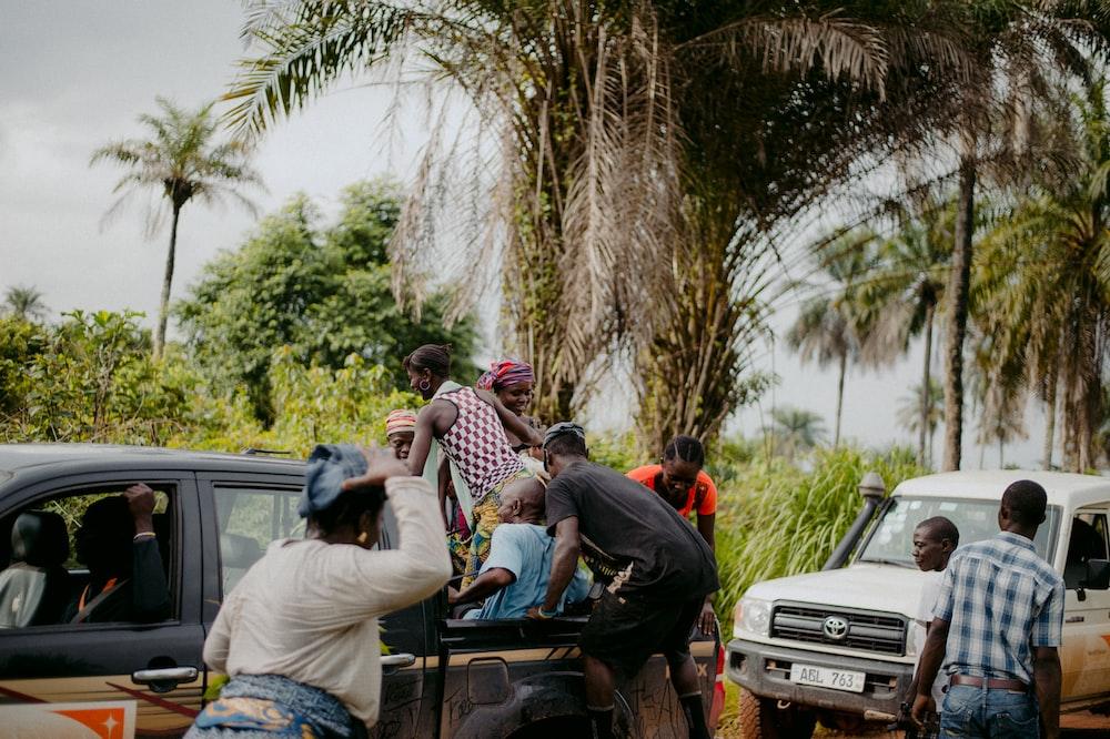 people sitting on black car during daytime