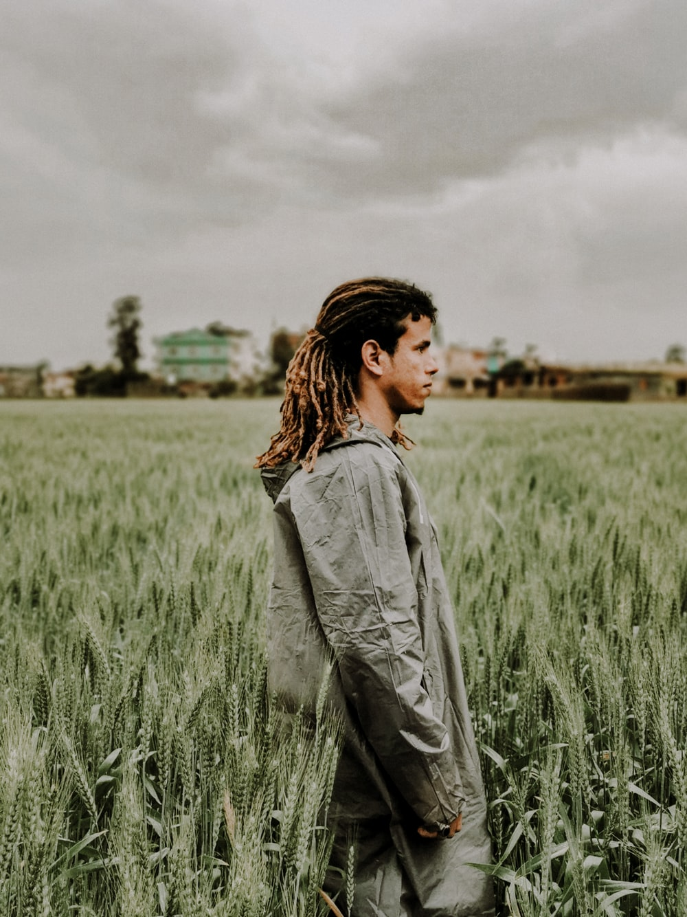 woman in grey denim jacket standing on green grass field during daytime