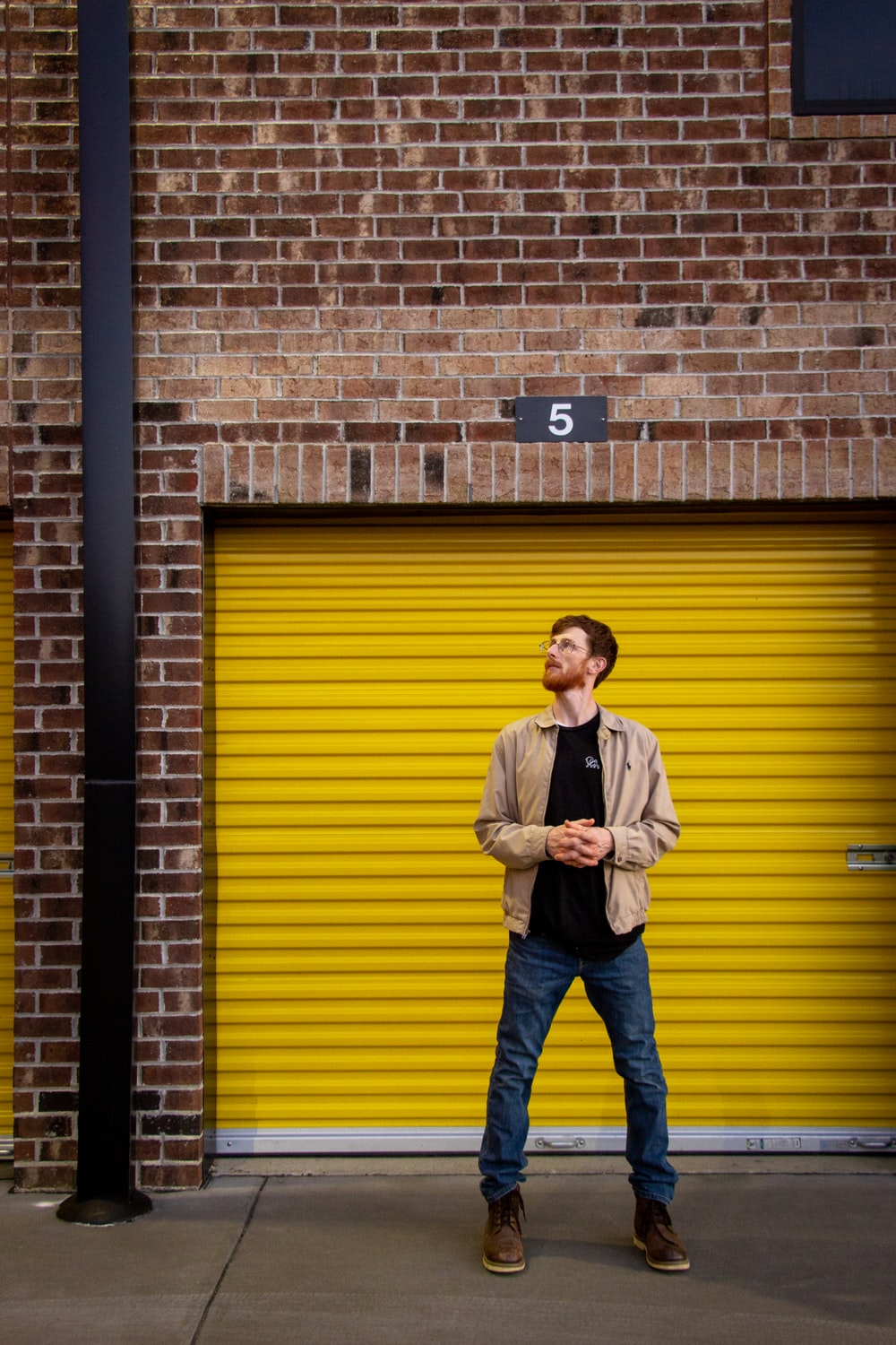 man in white dress shirt and blue denim jeans standing beside brown brick wall