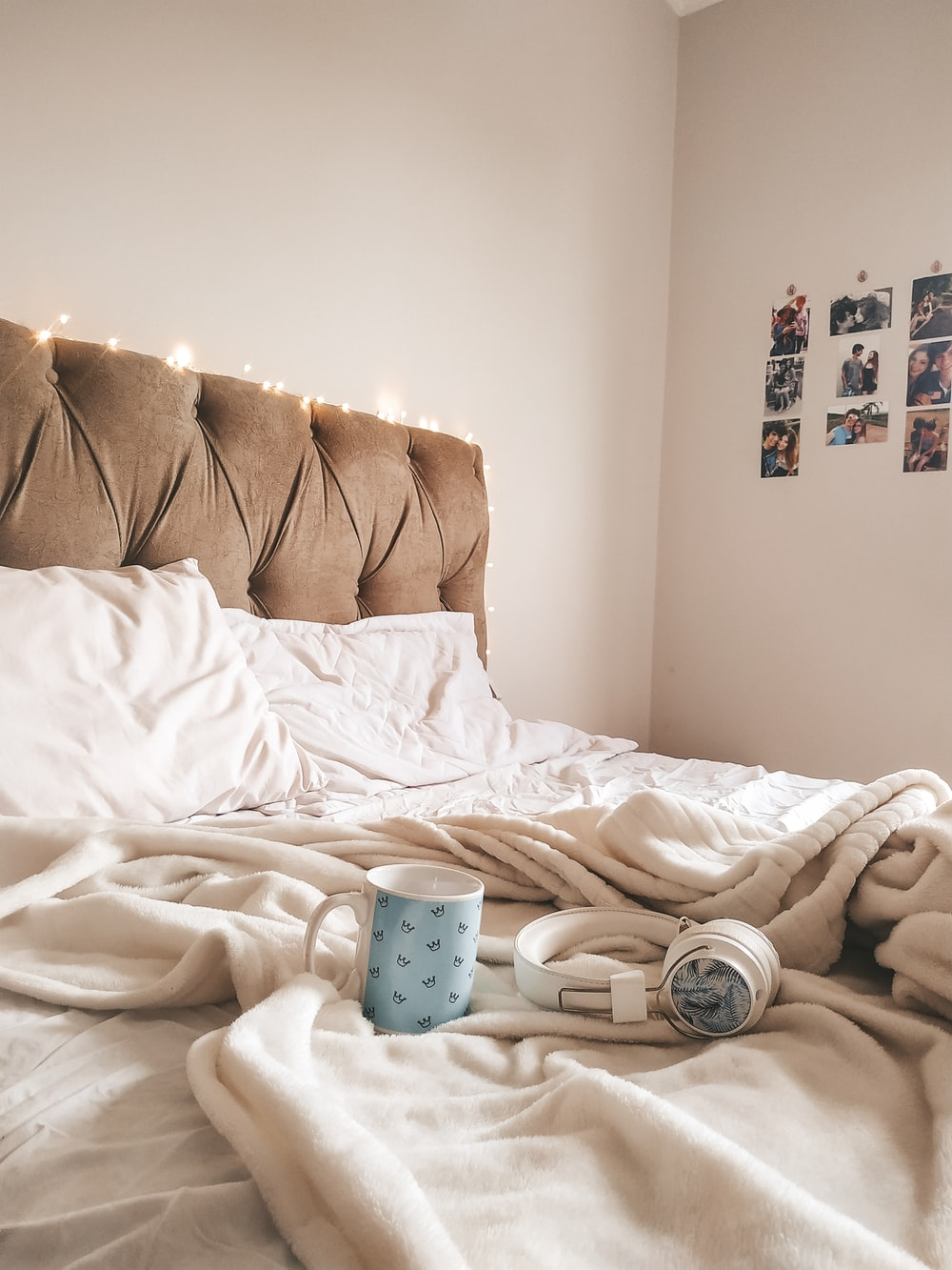 white and blue polka dot ceramic mug on white bed linen