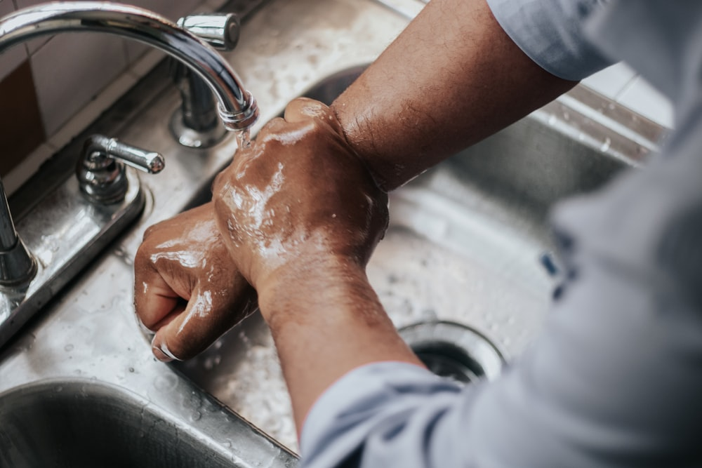 person in grey t-shirt washing hands