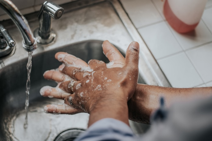 person in white shirt washing hands