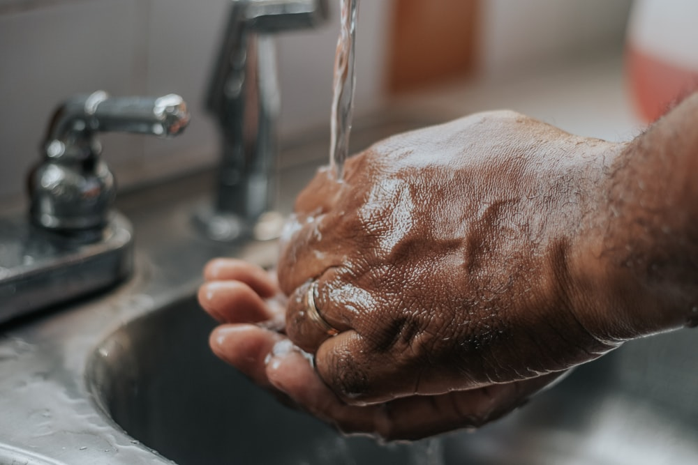 person washing hands on sink