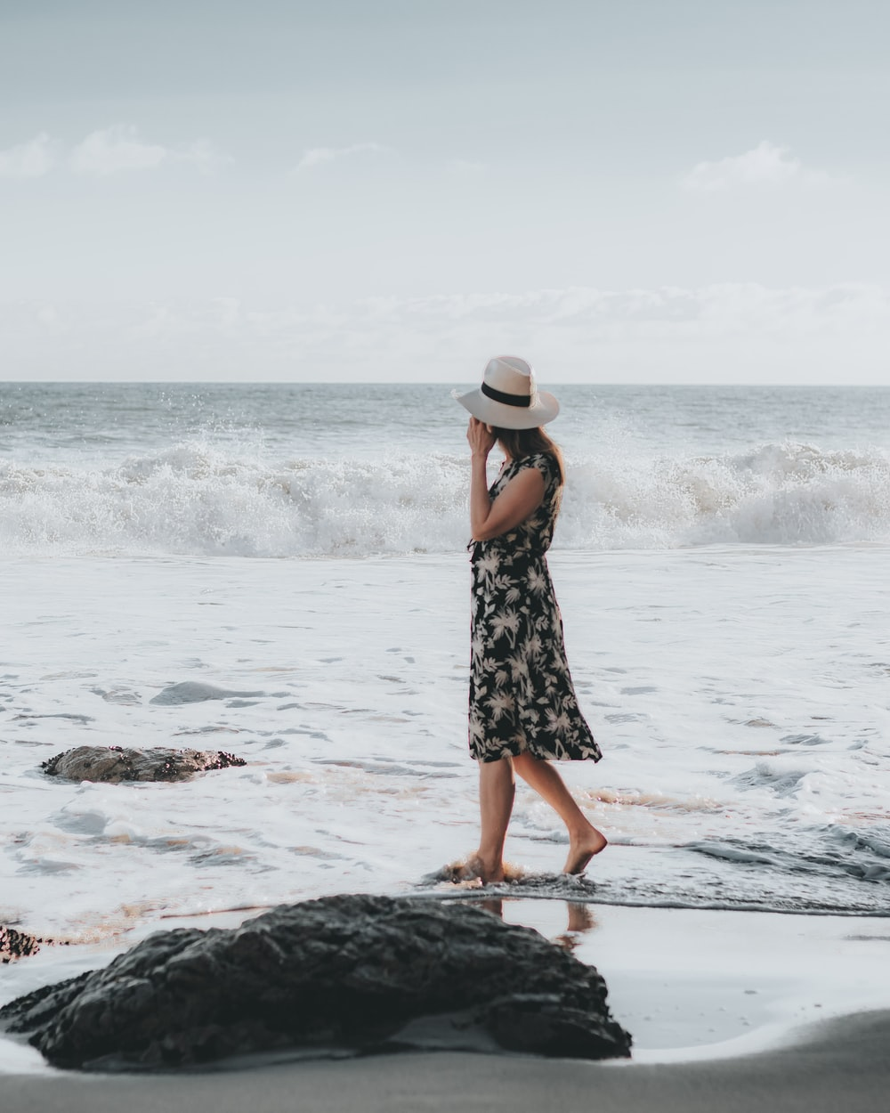 woman in black and white floral dress standing on sea shore during daytime
