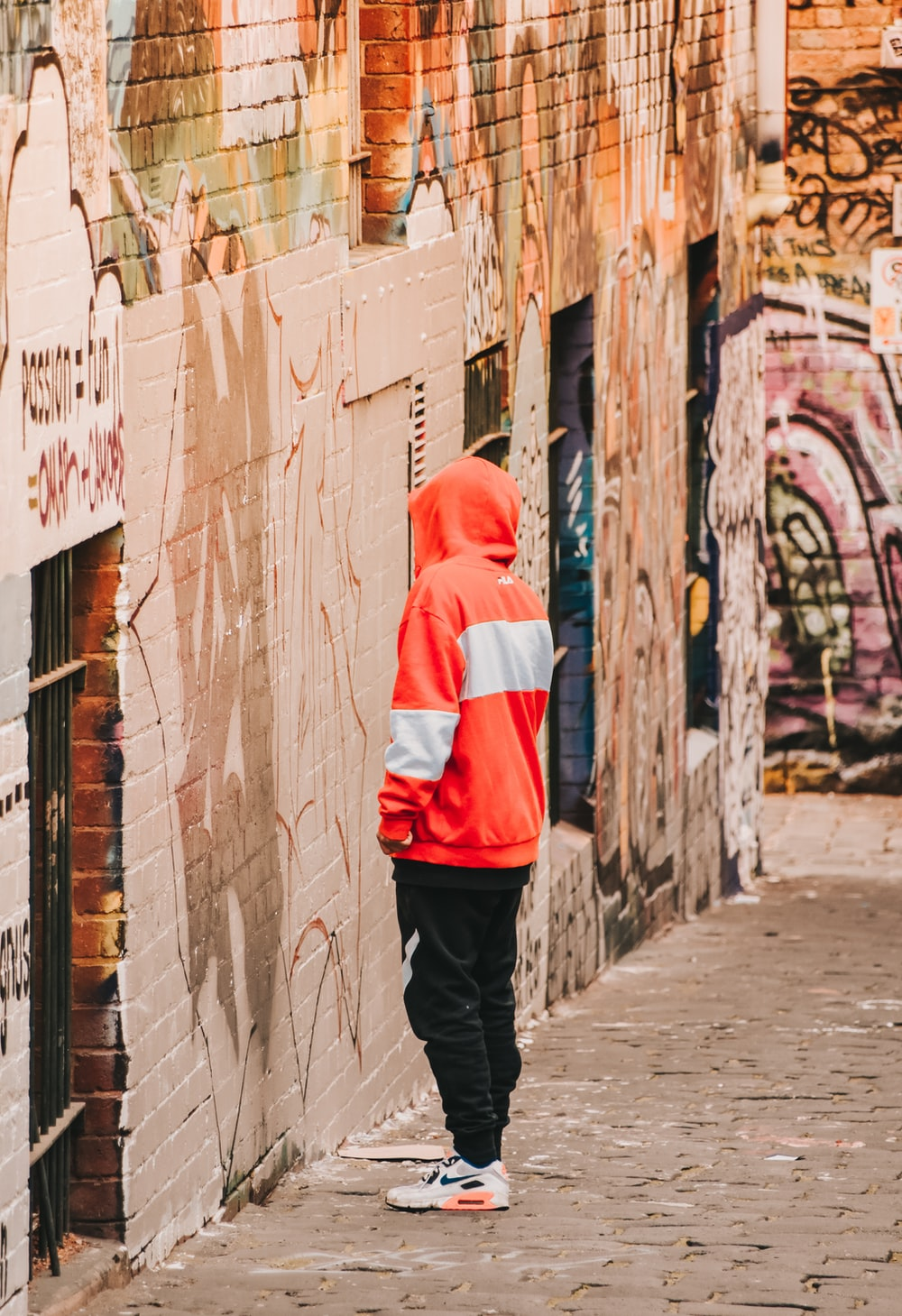 person in red and white hoodie standing on gray concrete floor during daytime