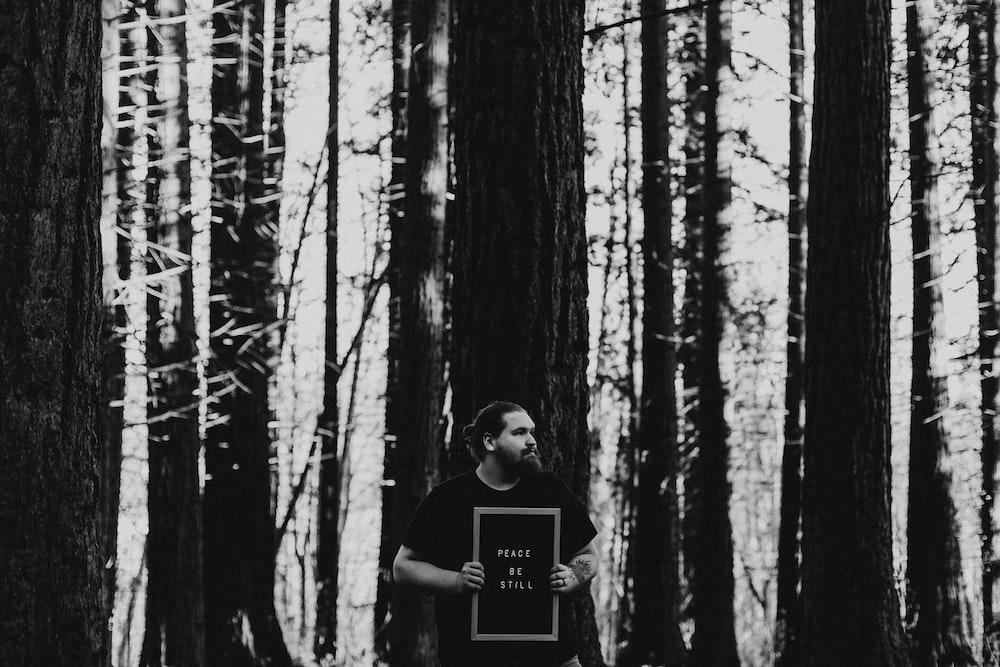 man in black crew neck t-shirt standing in the woods