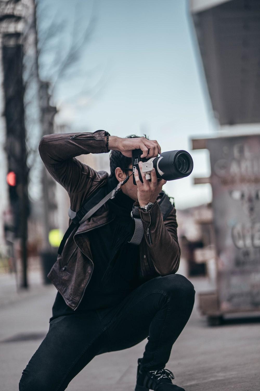 man in black jacket and black pants holding black camera