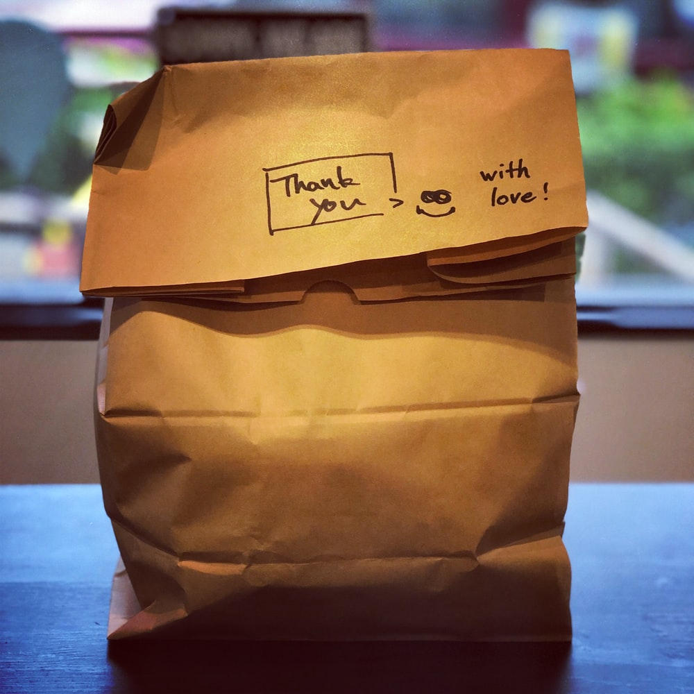 "brown paper bag with ""Thank you, with love"" written on it. Support local Winnipeg Metropolitan Region."