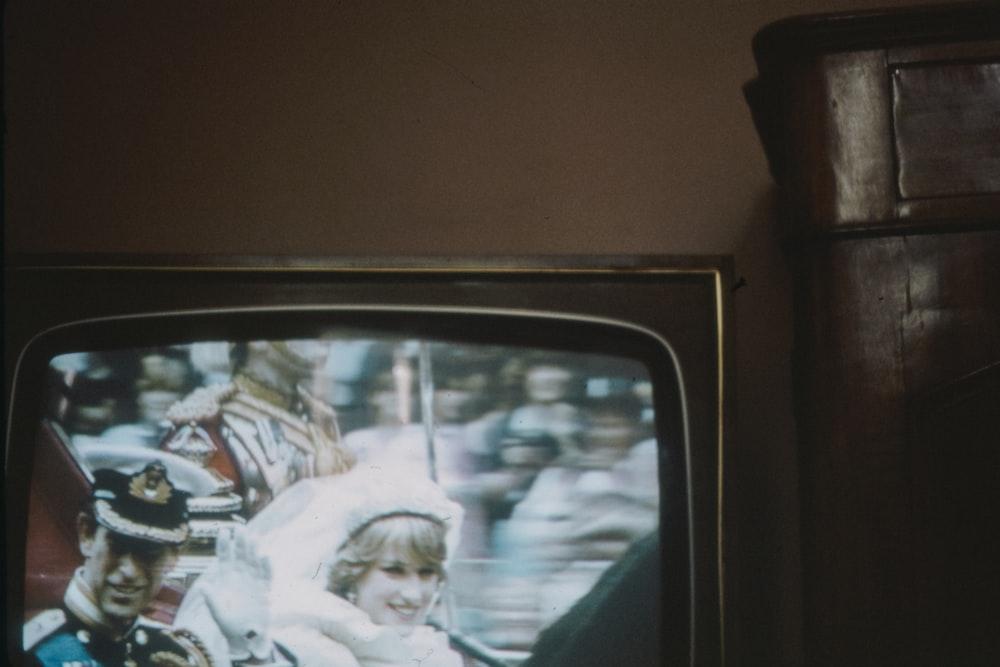 black crt tv turned on showing man in white dress shirt