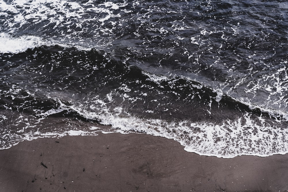 sea waves on brown sand during daytime