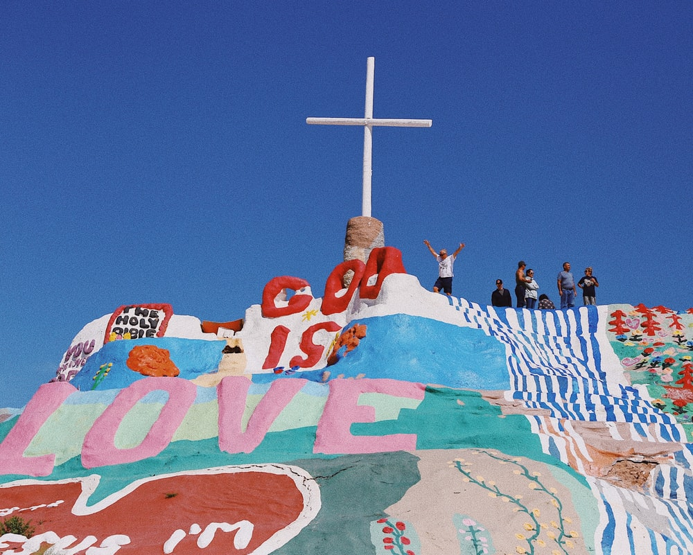 people standing on red and white concrete cross under blue sky during daytime