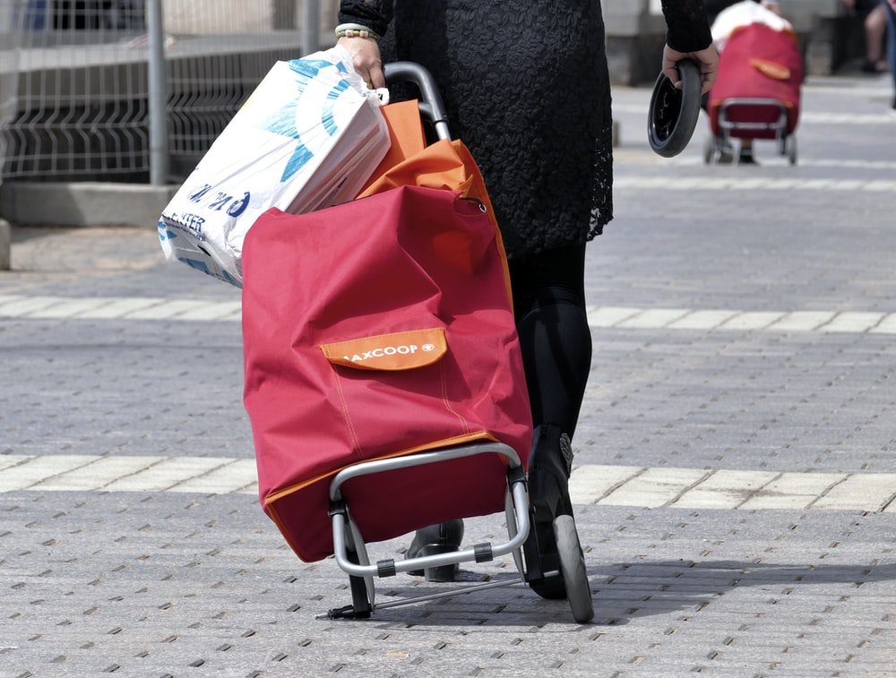 woman in black coat holding red and white tote bag