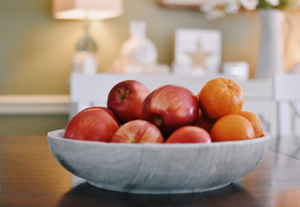 red apples on white ceramic bowl