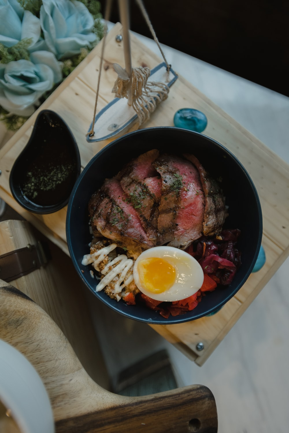 cooked meat with egg on black ceramic bowl