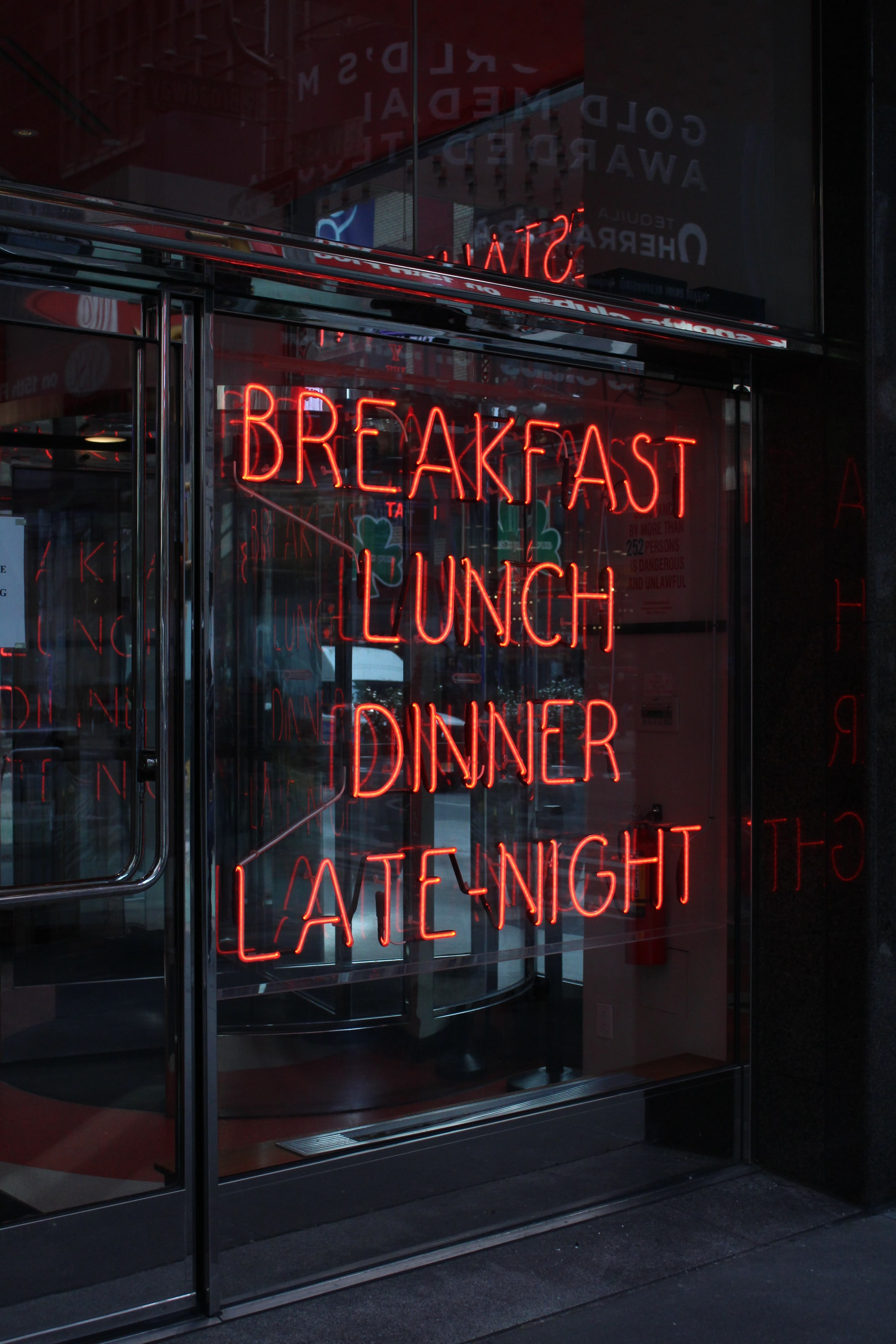 """A neon sign in a restaurant window, which reads """"Breakfast Lunch Dinner Late-Night"""""""