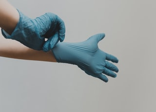 person in blue gloves and blue denim jeans