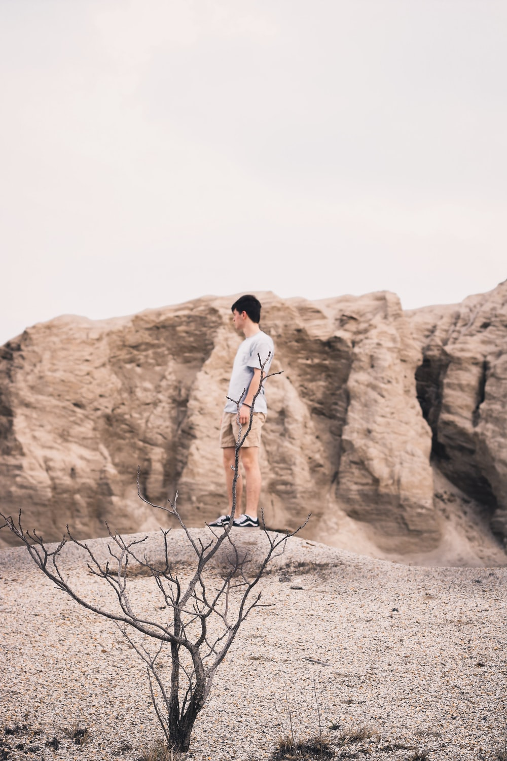 man in white t-shirt standing on brown rock formation during daytime