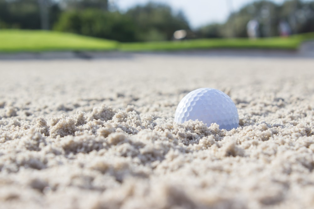 white golf ball on brown sand during daytime