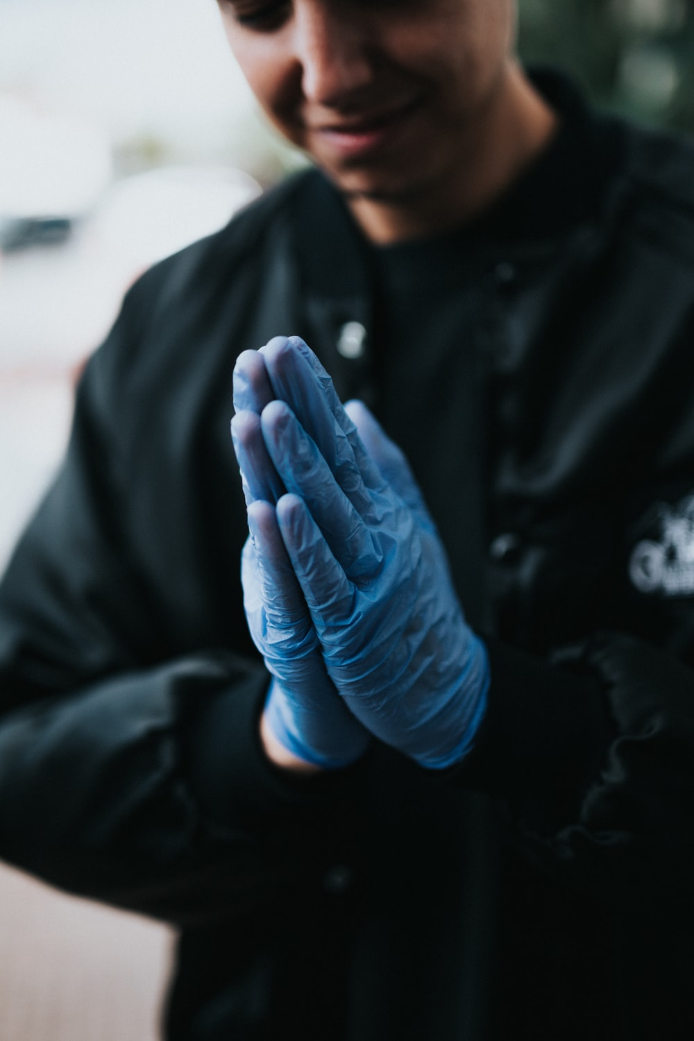person in black jacket with blue gloves