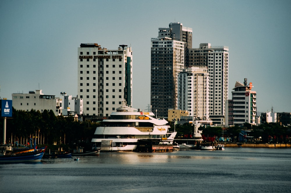 white and brown ship on water near city buildings during daytime