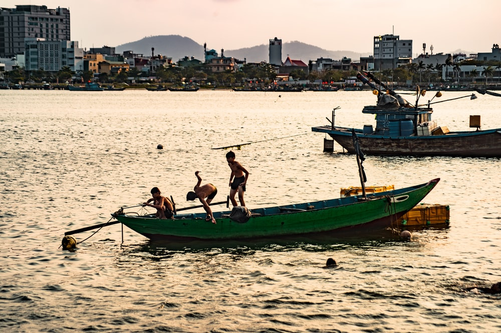 2 men and woman sitting on green and brown boat on beach during daytime