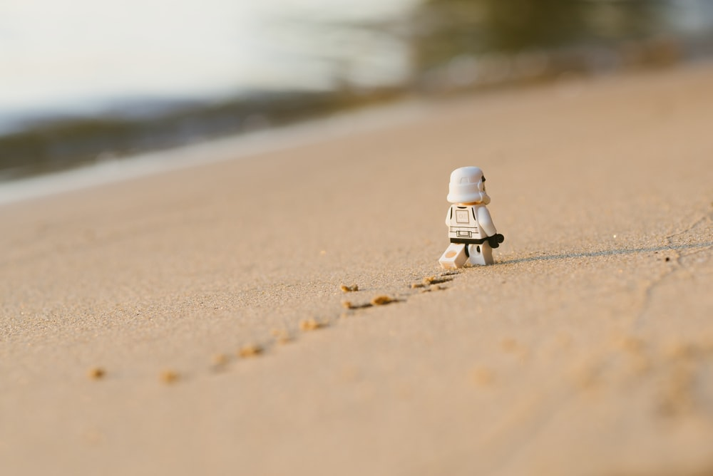 white lego toy on brown sand during daytime